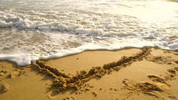 Heart drawn on the beach sand with sea foam and wave Footage