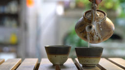 teapots pouring hot tea in tea cups at a table Footage