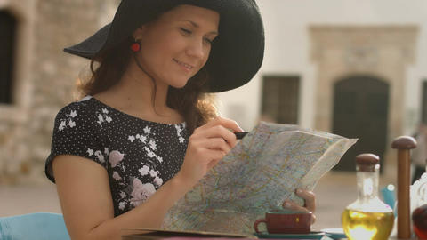 Happy young woman looking for interesting places to see, writing notes on map Footage