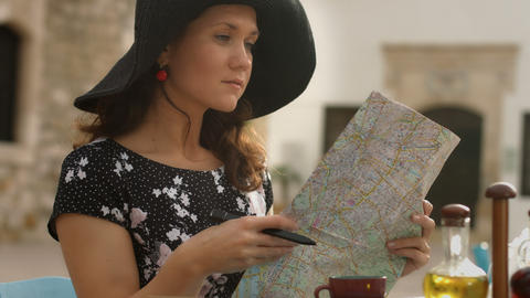 Elegant young female in cafe planning tour abroad, studying map, checking routes Footage