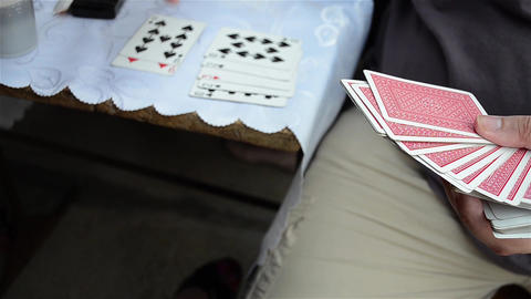 Woman draws a card game which is then placed on the table 3c Footage