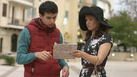 Young man helping pretty woman to find way to hotel, showing direction on map Footage