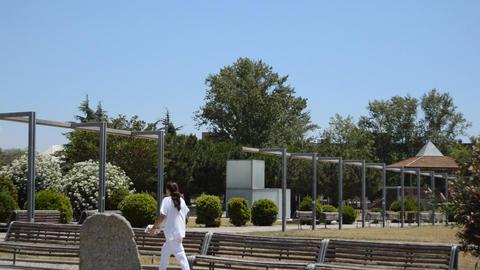 Nurse Walks In Park Near Hospital Footage