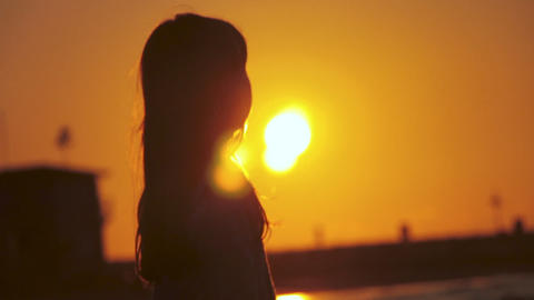 Back view of a silhouette of carefree unrecognizable girl enjoys a beautiful view of an exotic Live Action