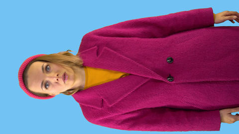 Young woman screaming, stress, in a red hat and a red coat on a blue background Live Action