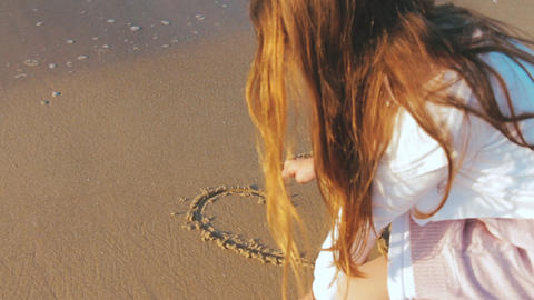 Carefree unrecognizable girl drawing a heart shape on the wet sand at exotic sunset Live Action