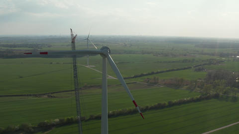 AERIAL: Wide View of Wind Turbine under construction being build on rich green Live Action