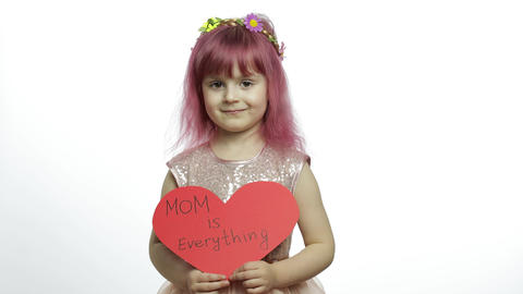 Child girl princess holds red paper heart with text about mother. Mother's day Live Action