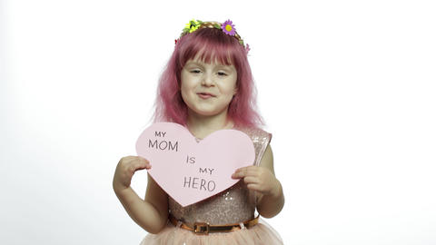 Child girl princess holds pink paper heart with text about mother. Mother's day Live Action