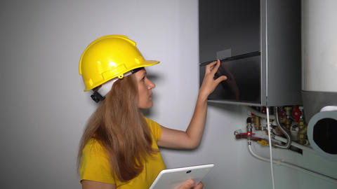 Skilled female heating specialist with tablet computer inspecting gas boiler Live Action