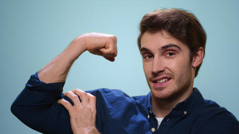 Young man showing biceps on blue background. Strong man posing at camera Live Action