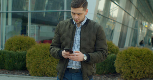 Portrait of Man walking near modern office center with Smartphone. Chatting in Live Action