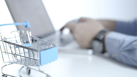 Cart on white desk and blurry a man using laptop for shopping online with credit card GIF