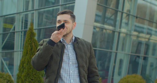 Man using a smartphone voice recording function online walking on a city street Live Action
