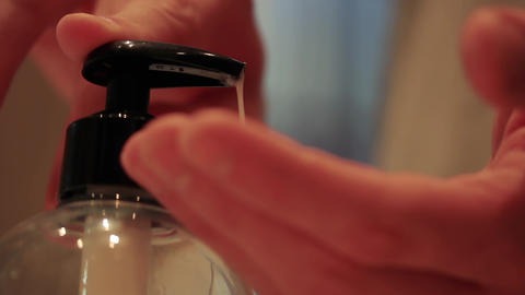 Man washing Hands at the Bathroom Sink using a Soap Dispenser. COVID-19 Prevention Live Action