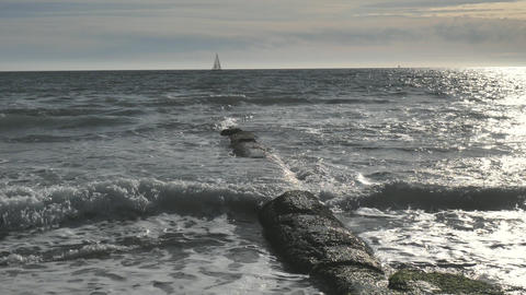 Stony breakwater pier in shore of the blue bay against the background of sailingboat at the horizon Live Action