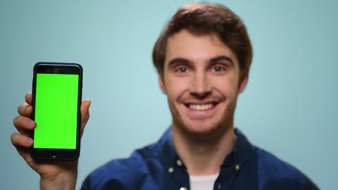 Man showing mobile phone with green screen.Student showing phone with chroma key Live Action