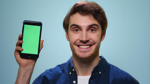 Man showing smartphone with green screen in studio. Student showing mobile phone Live Action