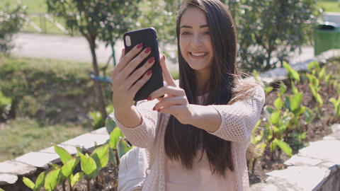 woman making selfie photo on phone camera outdoors Live Action