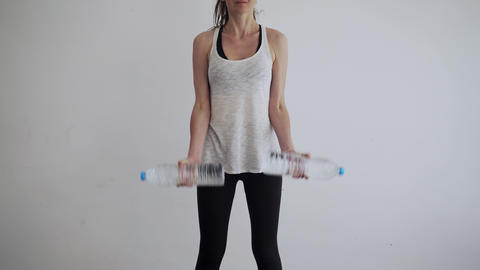 Sport at home. Workout at home. Girl doing exercises using plastic water bottles Live Action