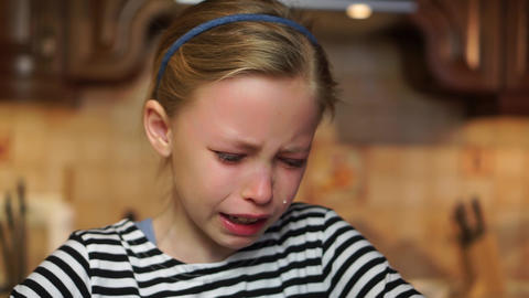 Blond child girl crying heavily tears drop down her face offended in home kitchen. Child abuse bad Live Action