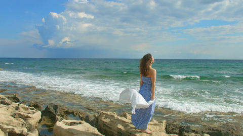 Beautiful brunette woman in maxi dress enjoying windy day on seashore, vacation Footage