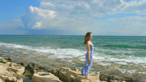 Happy woman standing on rocky beach, enjoying ocean breeze, waves coming ashore Footage