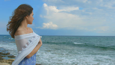 Lonely woman on beach, white scarf wrapped around her body. Marine landscape Footage