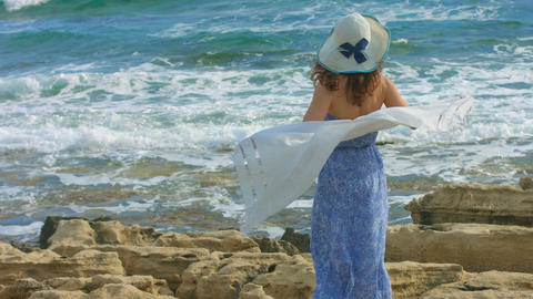 Slow-motion of attractive woman in long dress watching sea waves on rocky shore Footage