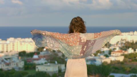 Woman enjoying sea breeze on hill, looking at seaside town. Feeling of freedom Footage