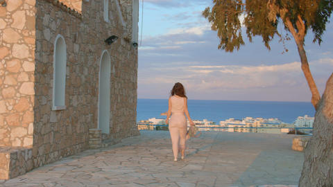 Beautiful woman walks on sidewalk, stops to enjoy amazing sea view. Resort town Footage