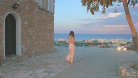 Attractive brunette slowly walking on sidewalk, enjoying view of seaside town Footage