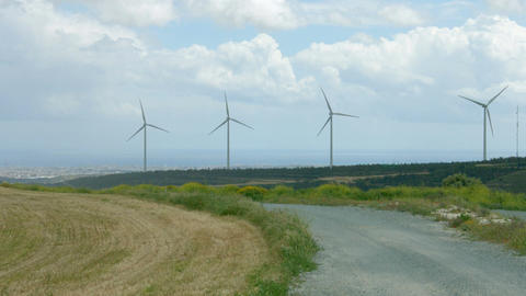 Abandoned road near modern windmills rotating on wind farm. Future technology Footage