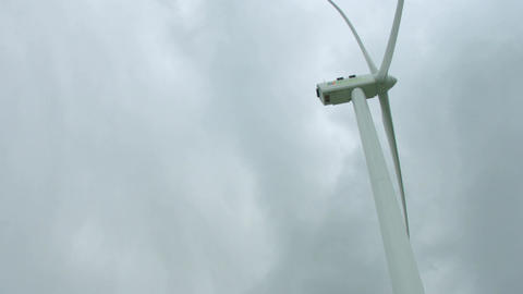 Huge wind turbine blades rotating under gray rainy sky, storm, vertical panorama Footage