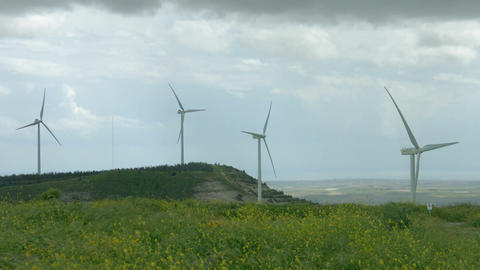 Wind turbine propellers spinning in wind, windmills in beautiful green field Footage