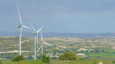 Beautiful rural landscape, green countryside, wind turbines rotating, mountains Footage