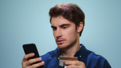 Man shopping online on smartphone. Guy using credit card for online payment Live Action