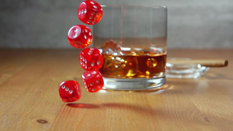 Whiskey in Highball on a Wooden Table and Dice. Slow Motion Live Action