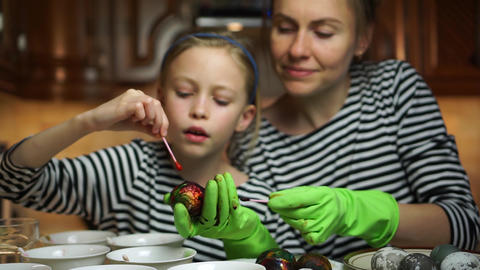 Easter family togetherness. Mother and child daughter in striped dress decorate Easter eggs together Live Action