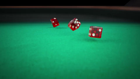 three red dice rolling on green game gambling table on black background, shooting with slow motion, Live Action