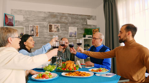 Young man clinking a glass of wine with his family Live Action