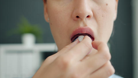 Close-up portrait of unhealthy young woman opening mouth taking pill indoors Live Action