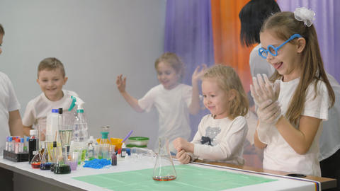 Chemical experiments for children. Girl dangles a transparent dish with ingredients. Bright emotions Live Action