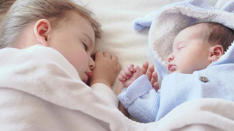 Childhood, infancy, family, sleep, rest concept - close up of two children Live Action