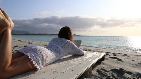 Young woman lying on sea shore reading a book at dawn in the wind, dressed in a white lace dress and Live Action