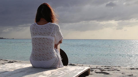 Young woman from behind sitting by the sea looks at the horizon at dawn in the wind, dressed in a Live Action