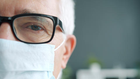 Close-up half face portrait of senior man in medical mask and glasses looking at Live Action