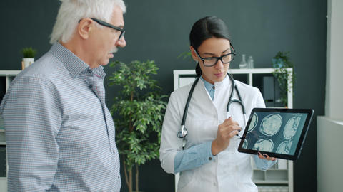 Young woman in uniform showing patient MRI images on tablet screen talking Live Action
