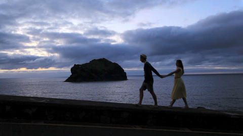 Young lovers man and woman walk along the night beach by the ocean. Romantic Live Action