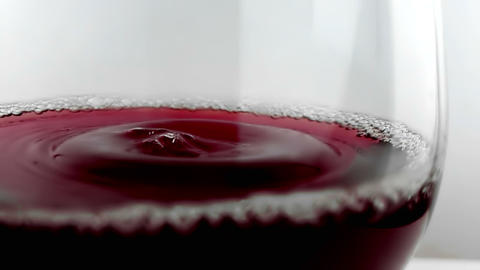 red wine drop falling down into drink glass on white background, nutrition health-care concept, Live Action